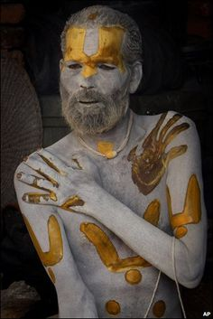 a sadhu applies ash and colored paste to himself in Kathmandu