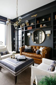 A brass and glass chandelier hangs over a blue ottoman coffee table placed on a beige rug in front of a caramel leather chesterfield sofa and between facing white swoop arm slipcovered accent chairs | Grove Park Construction