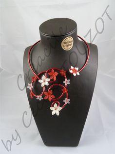 Collier en fil aluminium rouge et blanc.   Composé de perles de rocaille et de fleur lucite de différentes tailles rouges et blanches nacrées.   Un magnifique collier à arborer pour une occasion toute particulière ou bien pour habiller un décolleté de manière élégante et fantaisie.