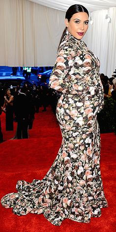 KIM KARDASHIAN - Met Gala 5-6-2013 So not what we predicted. Pregnant Kim wraps her bump in a custom Givenchy by Riccardo Tisci floral gown with grommet hardware at the sleeves, a turtleneck and a high slit. But the most bewildering aspect of the look? Those attached gloves.