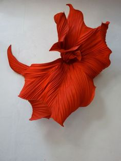 Peter Gentenaar- paper sculpture   Im interested in this piece beacause its a little different to some of his other pieces. Instead of being a dull yellow or blue its a bright vibrant orange. It almost looks as if it is trying to make a statement amoungst the other sculptures. The unusual shape also attracts my attension to this piece which i like. I would like my fmp to attract peoples attension to my work before others. Attract the eye in a crowded room.