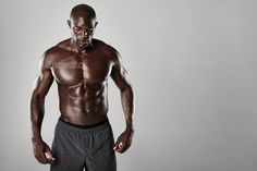 Shirtless male african model with muscular build by jacoblund. Studio shot of muscular man posing against grey background. Shirtless male african model with muscular build.