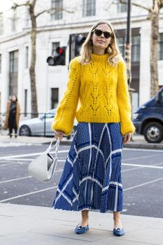 Yellow sweater paired with a blue and white print skirt, blue flats and a white purse.