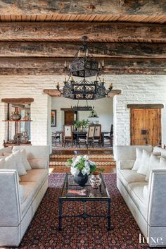 Whitewashed double-adobe brick walls provide a backdrop to one of two sitting areas in the great room. Designer Chandler Prewitt selected two white Milano sofas by Ebanista and a coffee table by Murray's Iron Works for the room's more formal side.