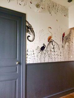 Le décor panoramique Metrozoo dans un couloir mis en valeur par une peinture gris foncé. Une réalisation de Nirjo Design. Crédit photo : Nirjo Design / Instagram. Papier peint en vente chez Au fil des Couleurs.