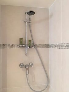 Marais designer 1BR, close to everything, up to 4 guest - Saint-Gervais Paris Airbnb, King Bedroom, Under Stairs, Exterior Lighting, Walk In Shower, Washer And Dryer, Kitchen Utensils, Basin, Saints