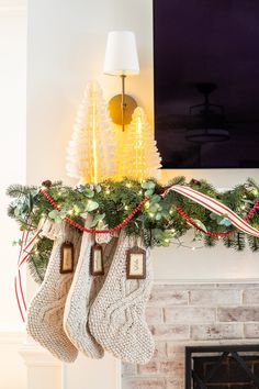 Swedish Christmas with paper tree figurines, chunky knit stockings, abundant greenery, fairy lights, and pops of red. #christmasdecor