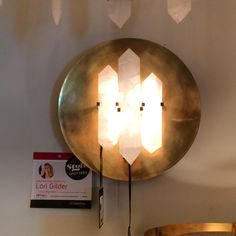 From the Halcyon collection Kelly Wearstler's round wall sconce for Visual Comfort is finished in natural quartz and antique burnished brass. The perfect blend of nature and hollywood glamor. Visual Comfort C&D Building 2G