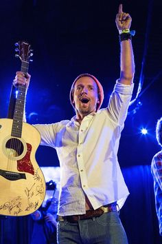 Jason Mraz shows off his autographed guitar during a performance at the Rob Machado Foundation 2nd Annual Benefit Concert on Nov. 11 in Solana Beach, Calif.