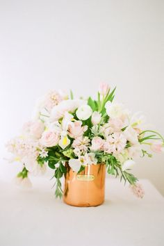 A gorgeous blush and white floral arrangement in a copper mug, a perfect centerpiece for a spring wedding!