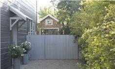 Corrugated steel panels as fencing and gate...wow!