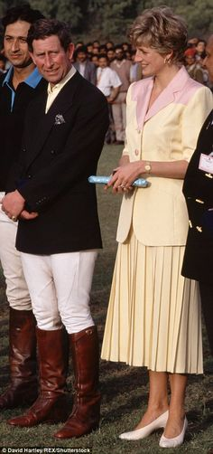 Standing slightly apart: The distance between Charles and Diana appears to be their choice. Soft yellow suit with pale pink shoulders.