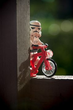 Lego Star Wars Storm Trooper riding a bicycle.