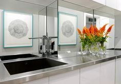 Stainless steel countertop and mirror splash back with white cupboards.  I want this for laundry