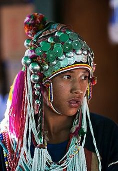 Myanmar, Burma, Keng Tung (Kyaing Tong). Young Akha girl wearing beautiful headdress decorated with silver coins and baubles, visiting Keng Tung market.