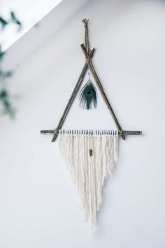 A dreamcatcher-esque wall hanging made with natural reeds, cotton string, and twine. A beautiful peacock feather hangs in the middle, and beneath it,