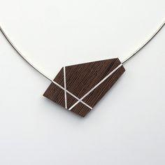 Dit collier bestaat uit een zilveren omega spang met een vaste hanger van wengé houten in de vorm van een vijfhoek. Deze vijfhoekige hanger is ingelegd met zilver en wekt de illusie dat de spang doorloopt in de hanger.Het collier heeft standaard een lengte van 50 cm, maar kan uiteraard ingekort of
