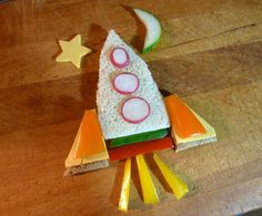 For the Rocketship:    2 slices white bread  1 slice whole wheat bread  Radish  Cheese slice  Assorted pepper slices  Cucumber slice  Cheese for star  Sandwich filling of your choice  Cut bread slices into a rocket shape from white bread. Fill with sandwich filling of your choice. Ham & cheese? Turkey and mayo? Cut rocketship legs from whole wheat bread. Cut cheese slice legs and orange pepper legs to add to the top of the whole wheat legs. Cut three thin radish slices to add for…