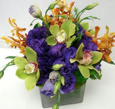 This is a cube vase floral arrangement that features lisianthus, cymbidium orchids and mokara orchids in a purple, lime green and orange color scheme.  See our entire selection at www.starflor.com.  To purchase any of our floral selections, as gifts or décor, please call us at 800.520.8999 or visit our e-commerce portal at www.Starbrightnyc.com. This composition of flowers is generally available for same day delivery in New York City (NYC). SQ058
