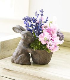 Fragrant lilacs, flouncy sweet peas, and delicate grape hyacinths are tucked into a Peter Rabbit-inspired planter (fill with floral foam; top with moss). Substitute your own tiny vessel for a similar effect.  - GoodHousekeeping.com