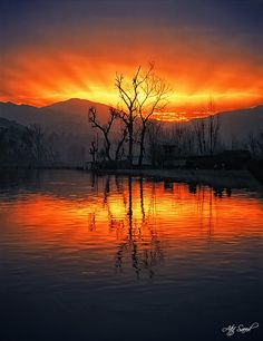 A Blazing Sunset...behind Mountains....with a Lake & Trees in the foreground