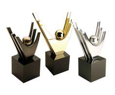 Peça: tridimensional, disponível em 3 tamanhos:  15cm de altura, base madeira com fórmica preta 8x8x8cm;  20cm de altura, base madeira com fórmica preta 10x10x10cm;  30cm de altura, base madeira com fórmica preta 12x12x12cm.  Materiais disponíveis: alumínio (prata) ou bronze (dourado ou patinado).  Placa cortesia: aço inox (prata) ou latão (dourada), 6x2cm.