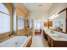 Big, bright master bathroom // Dual sinks, glass shower, jetted tub, oversized mirror