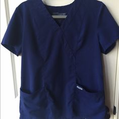 Greys Anatomy scrub top Navy Sz M Worn only a few times and in perfect condition. A navy scrub top by Greys Anatomy. I have a matching pair of pants listed (Sz small). The navy are my favorite in these scrubs, but I have multiple sets and am trying to clean out. This style is different from the signature as it cinches in the back instead. It's loose and comfortable and great for every day use. Greys Anatomy Tops