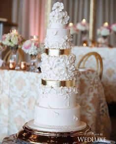 Seven tier wedding cake by @aelizabethcakes. So beautiful! #weddings #gold #white #floralart