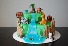 Zoo Cake - This zoo themed cake was for a 2 year old's birthday party.  The cake is white with vanilla mousse filling. The exterior is buttercream and the animals, tree, plants, rocks and sign are all fondant. The waterfall is sparkle gel icing and the wood posts are vanilla wafer rolls