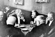 Erich Salomon, Albert Einstein engaging in animated conversation with British Prime Minister Ramsay MacDonald, surrounded by a group of luminaries including the Nobel Prize-winner Max Planck, far right, and other German political and business leaders, smoking cigars and sipping cognac. The reception was given by Reich Chancellor Brüning in honour of the visiting British Prime Minister in August 1931.