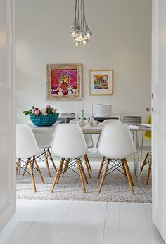Love this dining area. White walls allow the pictures to be a focus. The blue ceramic basket reflects colours in the paintings.