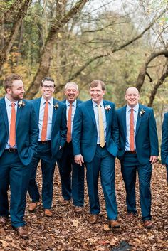 Groomsmen In Navy Blue Suits With Orange And Mustard Colored Ties