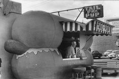View of Tail o' the Pup hot dog stand at its original location at 311 North La Cienega Boulevard. Historical Notes - Designed by architect Milton Black, the stand opened at La Cienega and Beverly boulevards in June 1946 to luminary-studded, searchlight-lit fanfare. Eddie Blake purchased the Pup in the early 1970s from its celebrity owners, the dance team of Veloz and Yolanda.