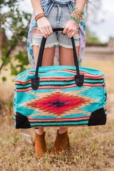"""Oversized weekender travel bag in bohemian style beautiful wool carpet makes our Southwestern Weekender Duffle Bag. This Southwestern blanket style wool carpet fabrics trimmed and accented in elegant brown genuine leather handles. Makes an amazing gym, weekend or travel bag. This bag is an oversized large weekender measuring 22""""L x 11""""W x 13""""H Color of the bag shipped will be assorted and may be any combo of the secondary picture showing all the colors."""