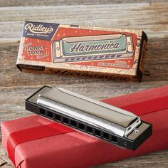 "HONKY TONK HARMONICA -- Classic noisy fun, this old-fashioned metal and plastic harmonica arrives in a retro-printed gift box and includes case and instruction sheet. Imported. 4-1/2""W x 1-1/4""D x 1-3/4""H."