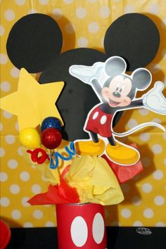 DIY Mickey Mouse table centerpiece! Colored card stock glued around empty formula can, Mickey die cuts glued to dow rods and placed in styrofoam block, finished with colored tissue paper!