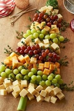 Christmas tree cheese board Cheese cubes, green and red grapes 1 celery stalk. Sprig of thyme