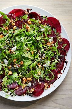This stunning winter salad gets its sweet, earthy flavor from roasted beets and balsamic vinegar. Creamy goat cheese and peppery arugula add color and balance, while toasted walnuts add crunch. A mandoline is the best way to get thin, even slices from the roasted beets. #salads #saladrecipes #healthysalads #saladideas #healthyrecipes