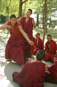 Maroon robed Tibetan Buddhist monks practicing philosophical debate, using the mala to illustrate a good point, coaching, argument, at His Holiness the 14th Dalai Lama's monastery in Dharamasala, India, on pilgrimage in 1992