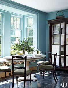 Farrow & Ball's Ballroom Blue paint brightens the breakfast area of a Connecticut home decorated by Miles Redd. Antique chairs flank a custom-made table by Redd.