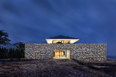 with a large gabion wall perimeter, the living areas of the house are elevated atop a private green roof yard for privacy and 360-degree panoramic views.