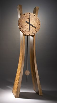 Stunning wood floor clock features a torsion box wrapped in zebrawood with a solid maple burl face with tapered legs. Ebony accents are inlaid into the clock face. The pendulum is ebony with a maple burl bob. Clock movement is high torque atomic quartz. Limited edition of 5, signed on back. Dimensions: 70.0in H x 23.0in W x 13.5in D $7600.00