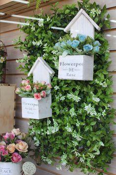 Follaje, flores artificiales, decoración con madera.
