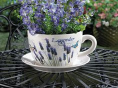 """Exquisite beauty and charming style! This teacup planter is ready to doll up your favorite greenery with its pretty design that features lavender blooms, butterflies and travel stamps. Drain hole in the bottom. Plant not included. Teacup: 9 1/4"""" x 7 1/2"""" x 4 5/8"""" high; plate: 9"""" diameter x 1 1/4"""" high. Material(s): DOLOMITEomite. Dimensions: 9.25"""" x 7.5"""" x 4.62"""""""