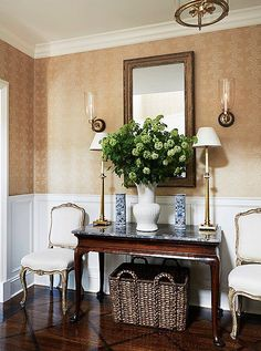 A pair of Louis-style accent chairs and gilded table lamps will add symmetry and glamour to any console table vignette.