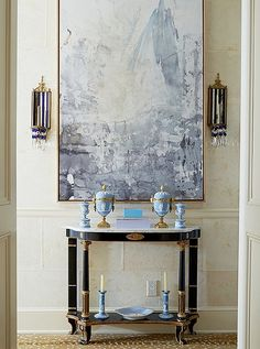 A French demilune styled with antique Wedgewood ceramics and a modern abstract painting makes for an eclectic and tasteful entryway vignette.