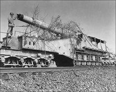 A large caliber Krupp K5 railway gun inspected by an American soldier