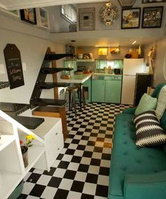 A black and white checkered floor with teal appliances create a retro theme in this tiny house.