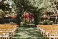 Garlands of red flowers form the backdrop for the outdoor ceremony | Gardener Ranch | Wanderlust Photo Co.